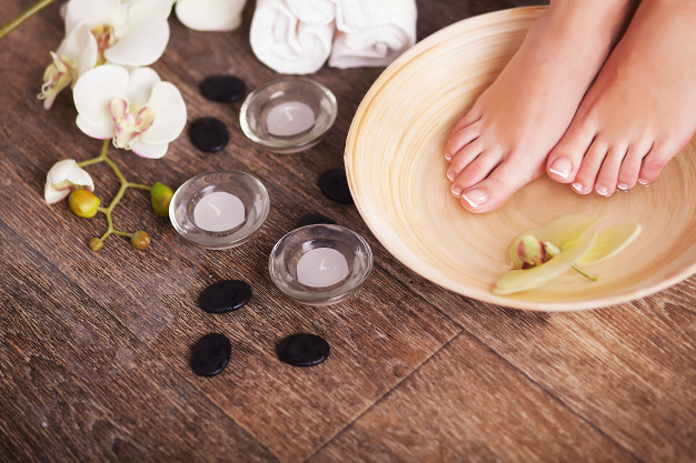 female feet with drops water spa bowls towels flowers candles